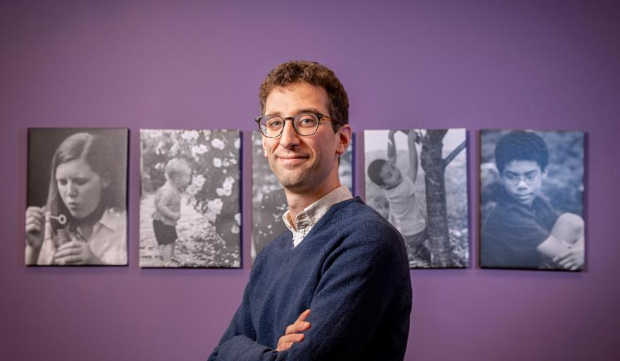 image of Schneider standing with arms crossed in front of purple wall and canvases