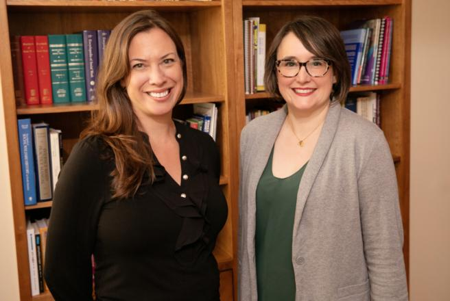 Professors Kate Wegmann Tara Powell standing together in conference room