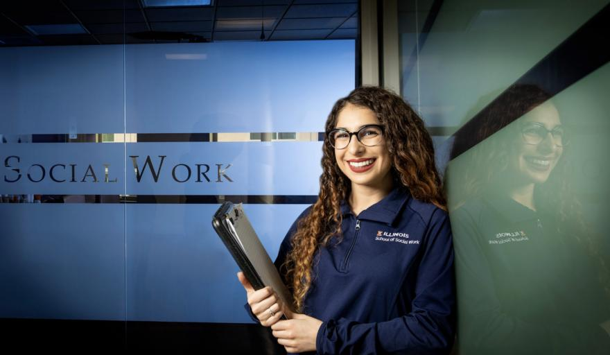 image of Scarlett Davalos standing at the School of Social Work, holding a folder