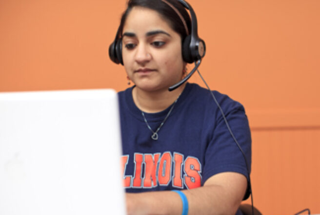 student using laptop and wearing headset