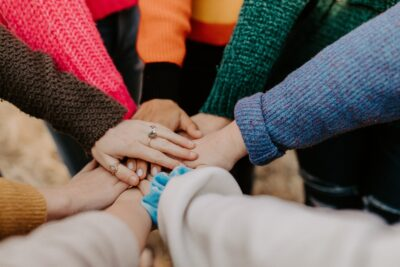 image of students with their hands together in a circle