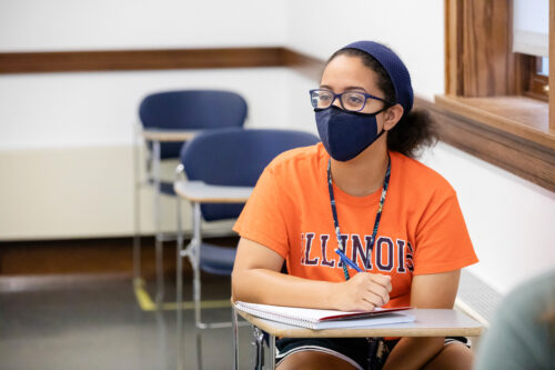 Female student with face covering takes notes in class.