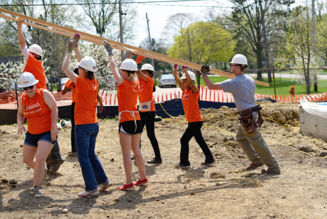students help build home, lifting rafter together