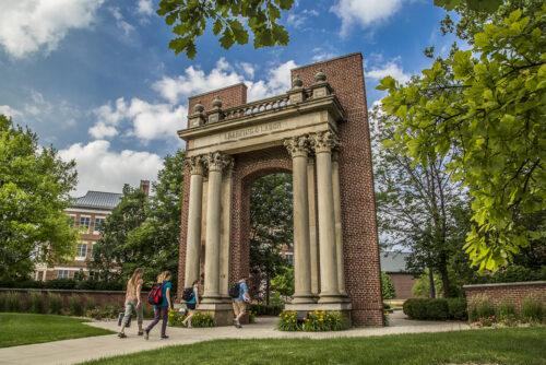 student walking under hallene gateway on urbana campus