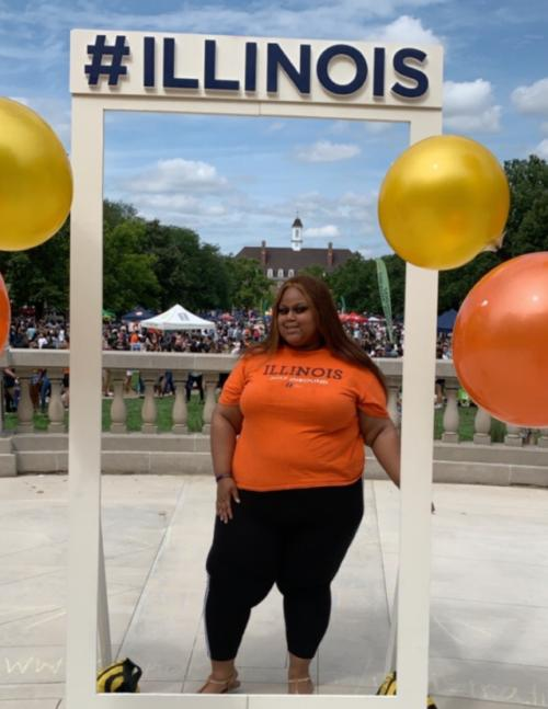image of Jahnellia Brown standing by ILLINOIS sign on campus