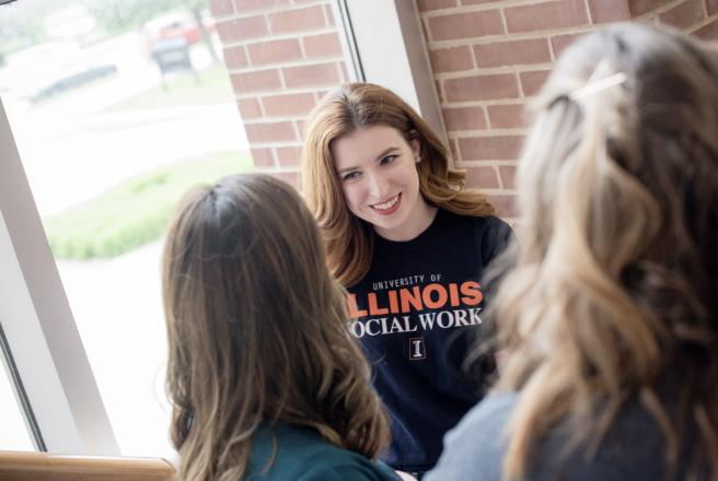 image of student speaking to others near window