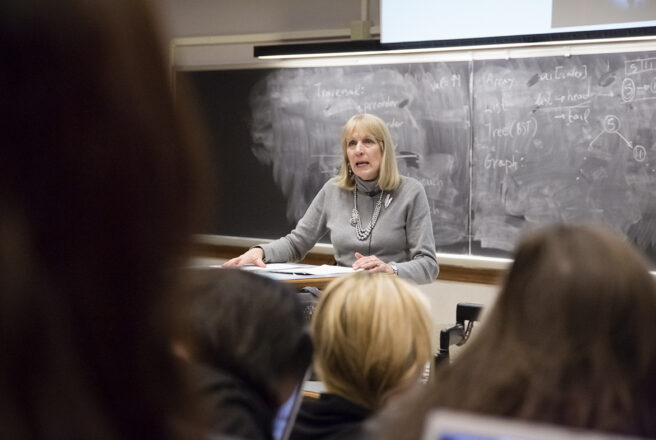 A female professor lectures in a classroom.