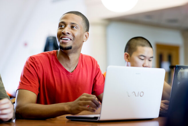 male student in red shirt smiling and using latptop