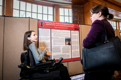 student presenting research poster to another person