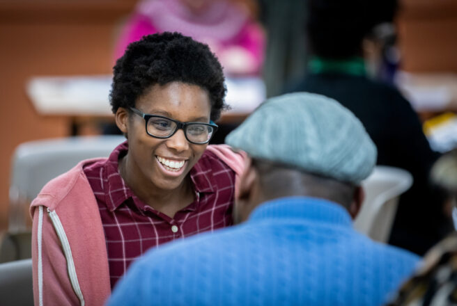 image of student smiling and speaking to another person