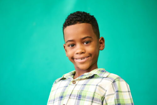 headshot of male youth smiling in front of green background